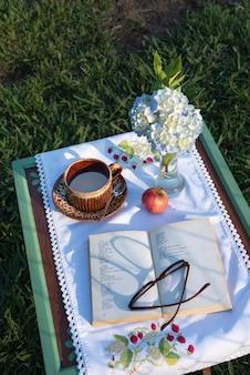 田舎のピクニックとして庭で読書とおやつを食べる