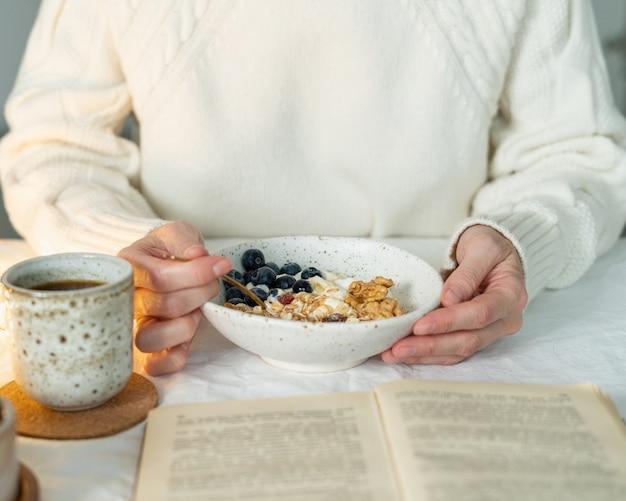 Чтение книги и здоровый праздничный зимний завтрак с мюсли