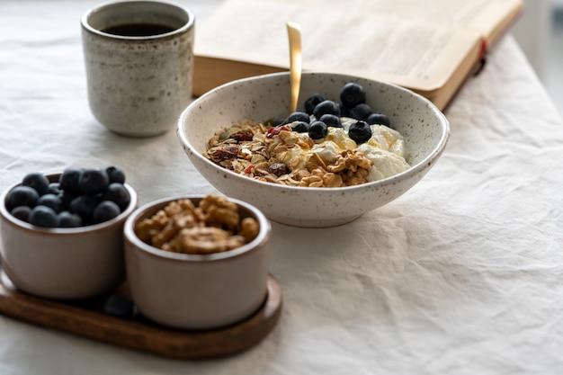 Чтение книги и завтрак здорового образа жизни с мюсли мюсли и йогурт в миске на белом столе, зерновая еда с орехами. органическое утреннее диетическое блюдо с овсяными хлопьями