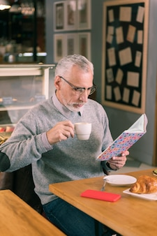 Reading book. bearded mature man wearing glasses reading book sitting in bakery and drinking coffee
