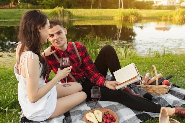 책을 읽고. 여름날 공원에서 함께 주말을 즐기는 백인 젊은 부부. 사랑스럽고 행복하고 쾌활해 보입니다. 사랑, 관계, 웰빙, 라이프 스타일의 개념. 진심어린 감정.