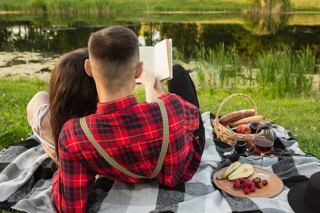 Reading book. caucasian young couple enjoying weekend together in the park on summer day