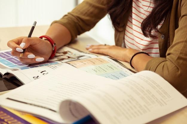 책을 읽고. 테스트를 수행하는 동안 테이블에 팔꿈치를 기대고 동기 부여 소녀의 닫습니다