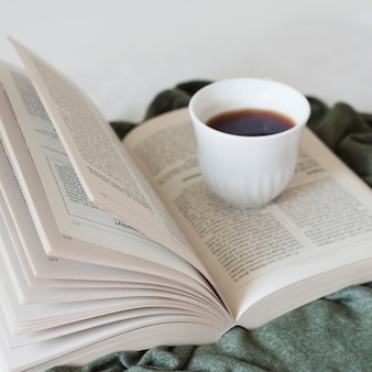 Reading a book and drinking coffee