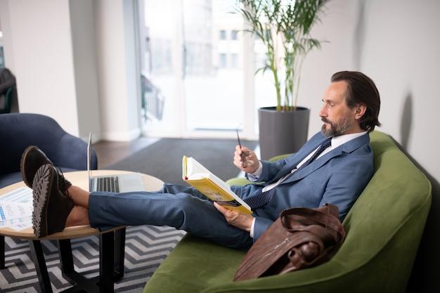 책을 읽고. 노트북과 함께 테이블 근처에 앉아있는 동안 책을 읽고 회색 머리 잘 생긴 사업가
