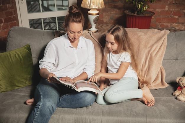 本を読んでいます。検疫中の自宅での自己断熱中の母と娘、居心地の良い快適な家族の時間、家庭生活。陽気で幸せな笑顔のモデル。安全、予防、愛の概念。