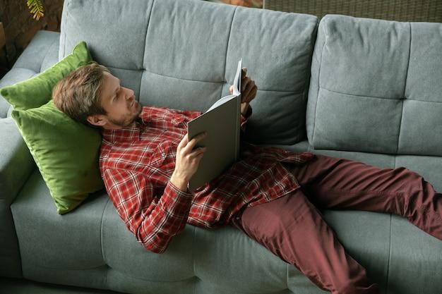 소파에 책을 읽고. 검역 기간 동안 집에 머무는 백인 남자