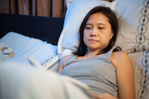 Чтение книги на кровати. азиатская женщина переворачивает книгу, чтобы прочитать свои книги перед сном. учитесь и расслабляйтесь в спальне ночью.