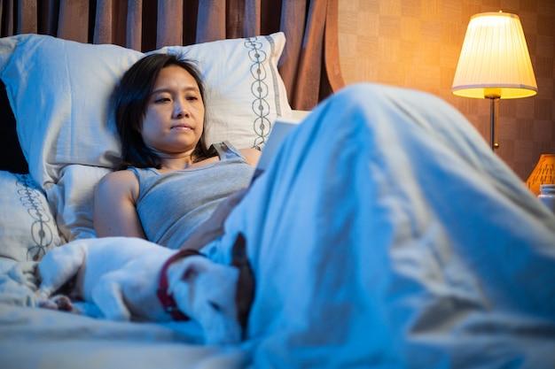Читает книгу на кровати. азиатская женщина переворачивает книгу, чтобы прочитать свои книги перед сном с собакой джек рассел терьер. учитесь и расслабляйтесь в спальне ночью.