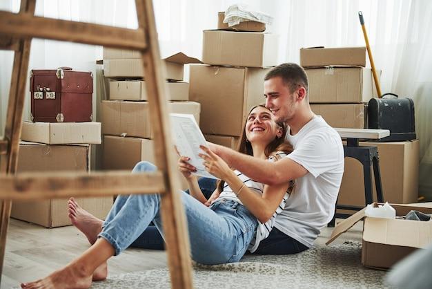 Чтение документа. веселая молодая пара в своей новой квартире. концепция переезда.