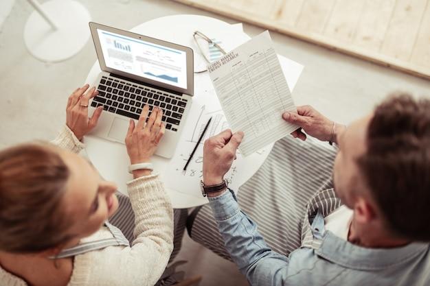 문서 읽기. 노트북 옆에 앉아 카페에서 함께 일하는 두 웃는 비즈니스 파트너.