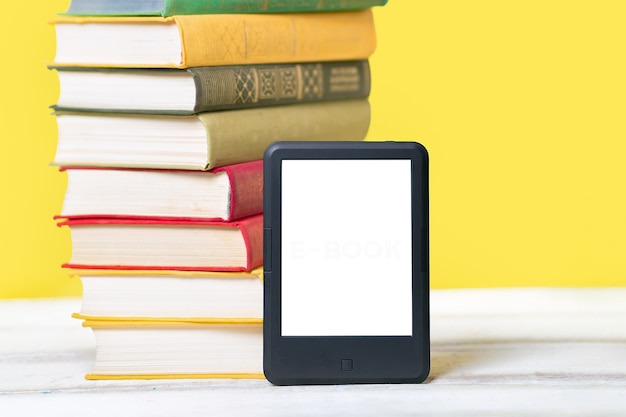 Reading. e-book reader and a stack of books on a yellow wall. concept of education and electronic gadgets.
