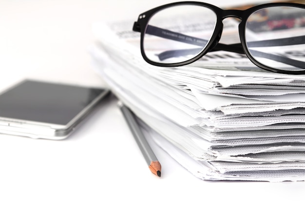 Reading eyeglasses with stacking of newspaper background