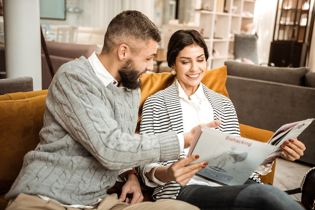Чтение мебельного каталога. позитивная яркая пара решает об оснащении будущих квартир, отдыхая на торговой мебели