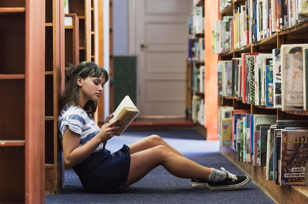 Reading girl sitting on library floor