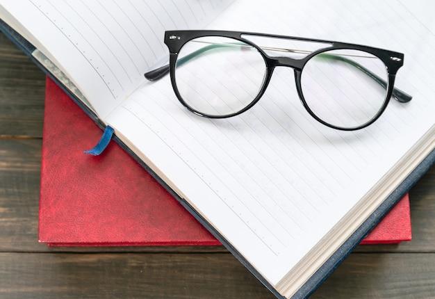 Очки для чтения положить на открытую книгу над деревянным столом