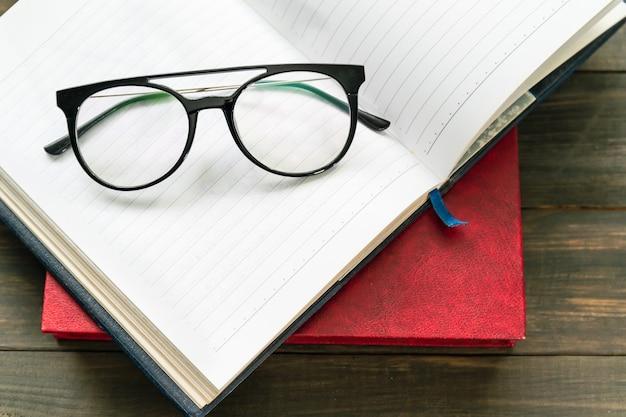 木製のテーブルの上に開いた本を置く老眼鏡