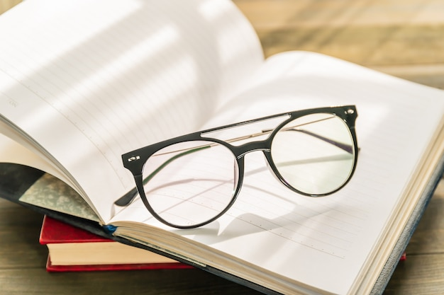 Reading glasses put on open book over wooden table