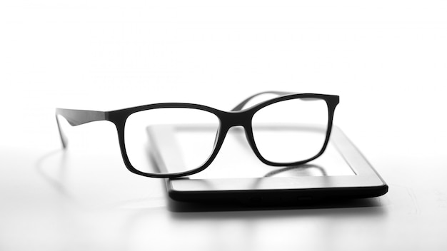 Reading glasses resting on an e-book reader
