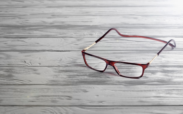 Reading glasses with flexible head band on wooden table