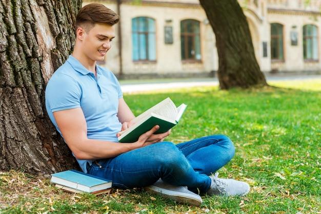 彼の好きな本を読んでいます。草の上や大学の建物の前に座って本を読んで自信を持って男子学生