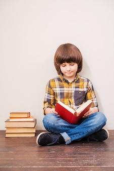 Читает свою любимую книгу. маленький мальчик читает книгу, прислонившись к стене со стопкой книг, лежащей рядом с ним
