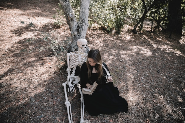 Reading lady in witch clothes hugging skeleton