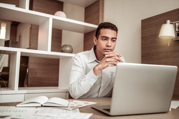 Reading letter. young businessman reading important business letter on his laptop sitting in hotel room