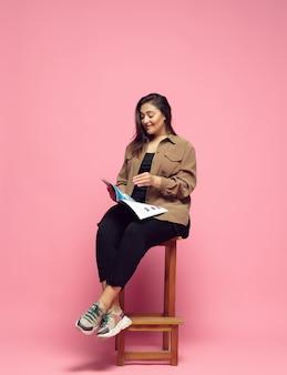 잡지 읽기. 분홍색 배경에 평상복을 입은 젊은 여성. bodypositive 성격, 페미니즘, 자신을 사랑하는 것, 아름다움 개념. 플러스 사이즈 사업가, 아름다운 소녀. 포용성, 다양성.