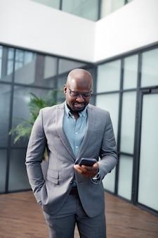 メッセージを読んでいます。スマートフォンでメッセージを読んで笑っているアフリカ系アメリカ人の実業家