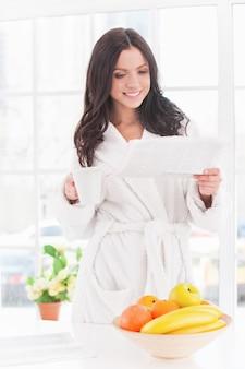 朝のニュースを読む。一杯のコーヒーと新聞を読んでバスローブで美しい若い笑顔の女性