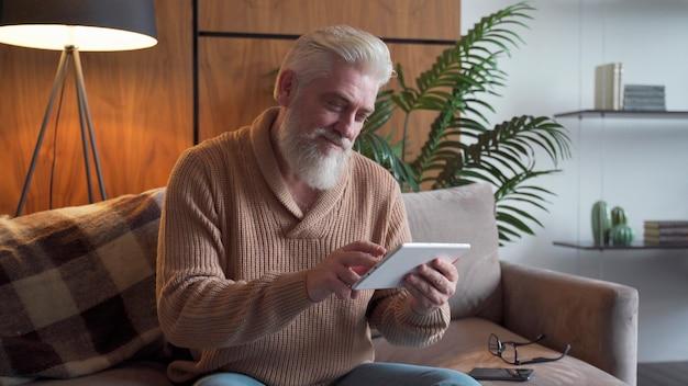 Чтение новостей. старший мужчина с седой бородой с помощью цифрового планшета сидит на диване у себя дома