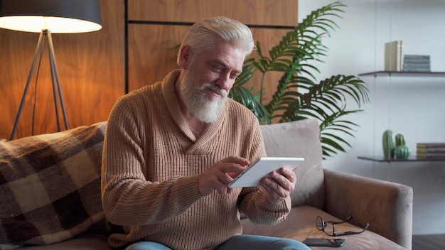 Reading news. senior man with a gray beard using digital tablet sitting on the couch at home