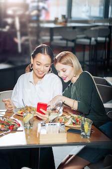 ニュースフィードを読んでいる 2 人の親友が夕食中に赤いスマートフォンで好奇心をそそるニュースフィードを読んでいる