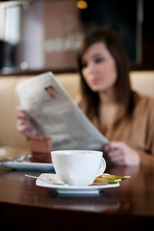 Reading newspaper in cafe