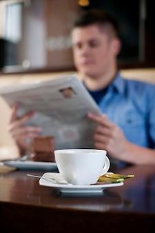 Leggendo il giornale nella caffetteria