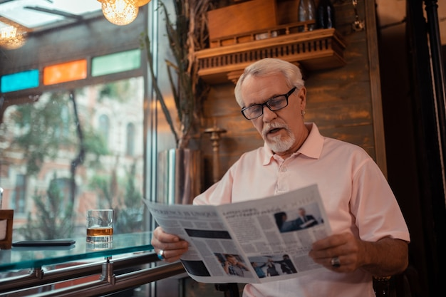 Reading newspaper. grey-haired man wearing glasses reading newspaper sitting in pub