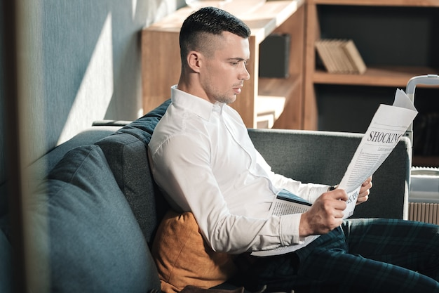 Reading newspaper. young handsome businessman sitting on sofa reading newspaper in the morning
