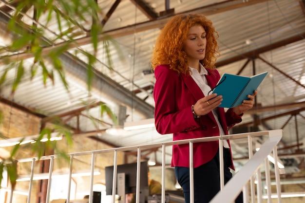 Чтение заметок. рыжая деловая женщина читает заметки в блокноте во время планирования дня