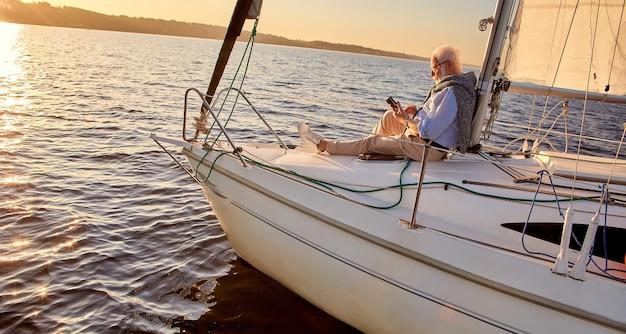 ヨットやヨットのデッキの横に座っているリラックスした年配の男性の船上側面図を読んでください