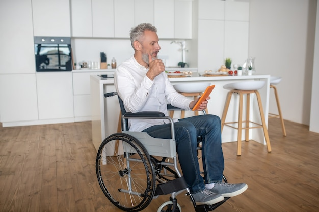Reading online. gray-haired handicapped man with a tablet in hands