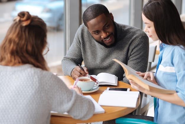 시 읽기. 국제 학생들과 함께 테이블에 앉아있는 동안 관심이 책을 들고 꽤 젊은 아시아 소녀.