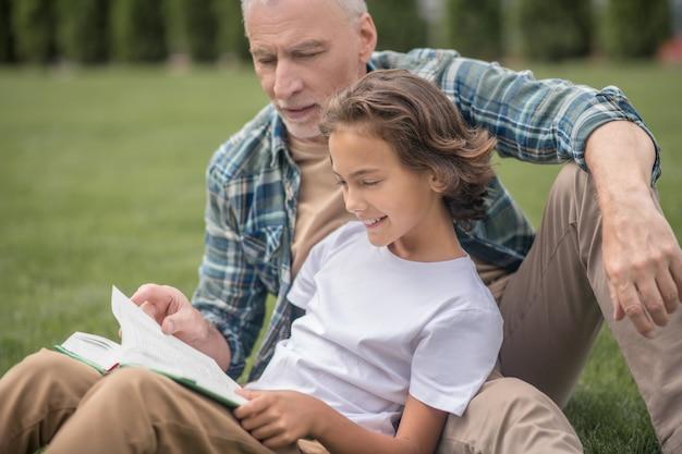 読書。一緒に座って本を読んでいる息子とお父さん