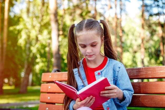 本を屋外で読む。本を読んで、ベンチに座っている十代の少女。