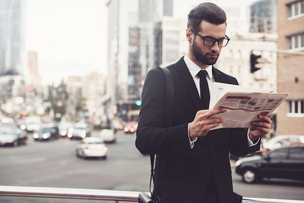 最新のニュースを読む。新聞を読んでフルスーツで自信を持って若い男