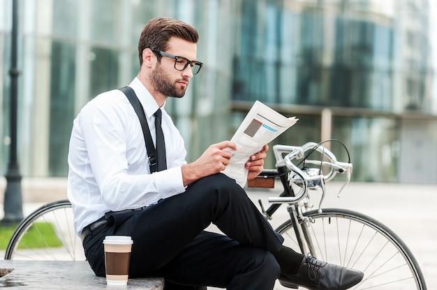 最新のニュースを読む。バックグラウンドでオフィスビルと彼の自転車の近くに座って新聞を読んでいる青年実業家の側面図