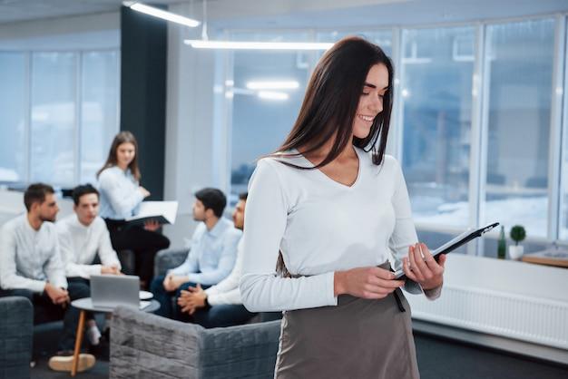 レポートを読む。バックグラウンドで従業員とオフィスに立っている若い女の子の肖像画