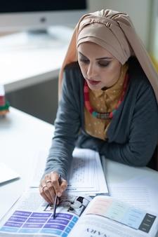テキストを読む。テストを修正しながらテキストを読んでヒジャーブを身に着けている若いイスラム教徒の教師