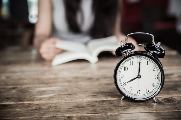 읽기 시간, 여자와 나무 테이블에 8시에 시계 책을 읽고 배경 흐림.