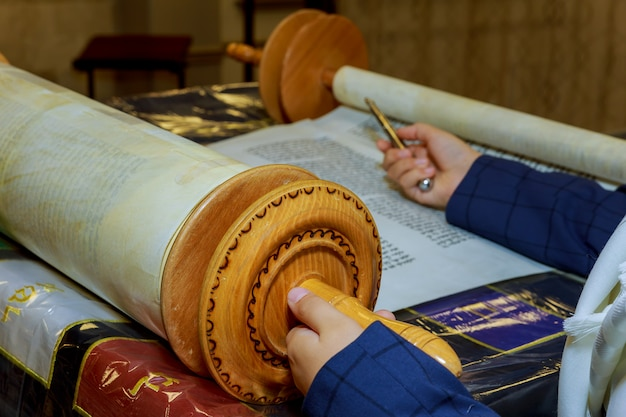 Reading a torah scroll during a bar mitzvah ceremony .